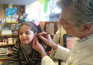 Pharmacien dessinant des points sur les oreilles d'une fillette