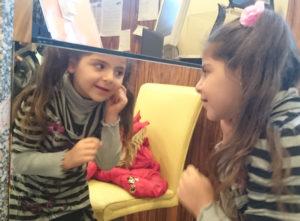 Petite fille devant un miroir, heureuse de pouvoir porter des boucles d'oreilles.